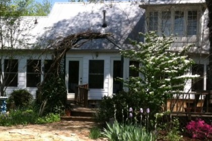 White wood sided 1-story building with blue bird bath, purple iris and shade trees around front wood deck.