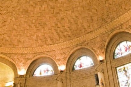 Beige and brown brick domed ceiling with stained glass arched windows ringing the walls of the basilica.