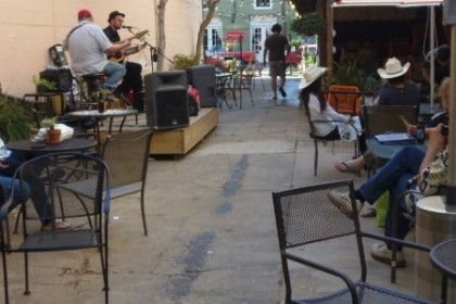Narrow patio enclosed by brick walls with black metal mesh tables and chairs and people listening to a live band.