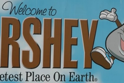 Blue vinyl sign with a silver Hershey Kiss character with words reading Welcome to Hershey the Sweetest Place on Earth
