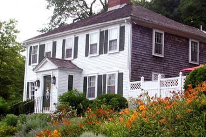 2 story white and gray cape cod colonial with orange and yellow flowers.