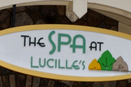 White oval sign with gold border and the words The Spa at Lucille's