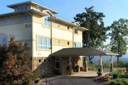 3 story building of rock and stucco with covered portico over circular driveway.