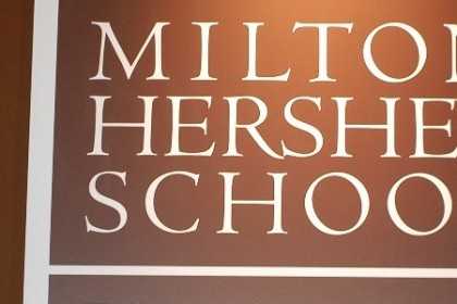 Dar brown square sign with white border and white letters that read Milton Hershey School