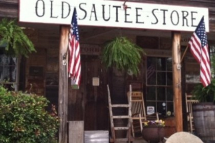 White sign reading Old Sautee Store across front of wood porch with 3 US Flags and antiques.
