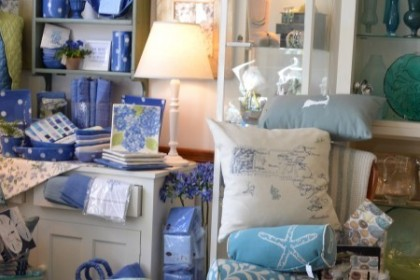Gift shop display of blue candles, blue print pillows, and deep blue accessories.