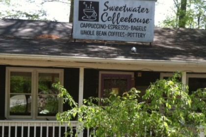 Gray wood building with white painted rail porch and sloping roof with white sign reading Sweetwater Coffeehouse.