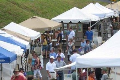 Blue, white and beige pointed top canopy craft tents lined up with people walking and looking at art displays.