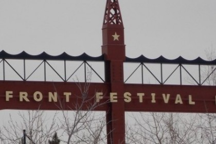 Rusted metal span, with cut out stars and the words Bayfront Festival park with de-leafed trees and gray sky.