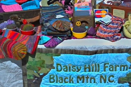 Bright, multi-colored socks and hand woven small garments on table with sky-blue fabric sign reading Daisy Hill Farm