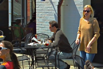 Sunny outside patio seating at a restaurant with pale blue painted brick, and people eating food and walking around.