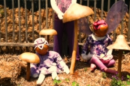 Gourd figures resting in straw bales in front of brown wooden slat fence and oversize golden brown mushrooms.