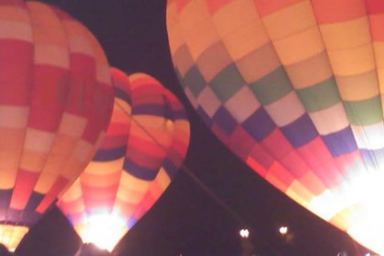 5 multi-colored hot air balloons inflated and glowing in a dark night sky.