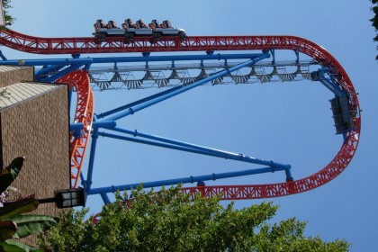 Red metal roller coaster framework with 3 white cars zooming to the next turn.