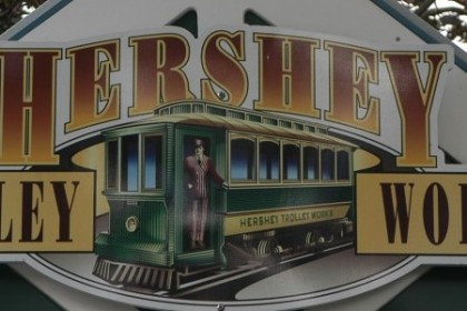 Large white wooden sign with a green and yellow vintage trolley in the middle and the words Hershey Trolley Works.