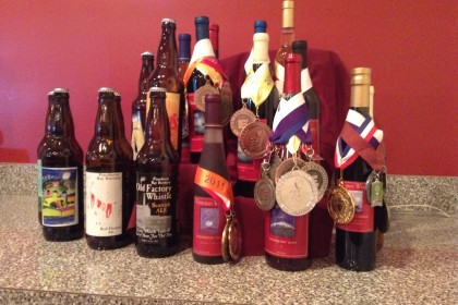 12 brown glass beer bottles with multi-colored and varied labels and award ribbons and medals.