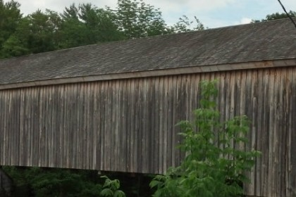 full span of a wooden covered bridge with very weathered wood side and roof