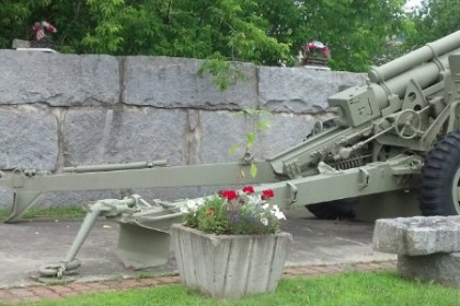 Howitzer Canon mounted on concrete with stone wall at side