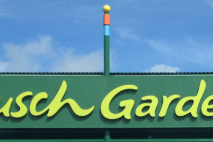 Bright blue sky and green horizontal sign with bright yellow letters reading Busch Gardens