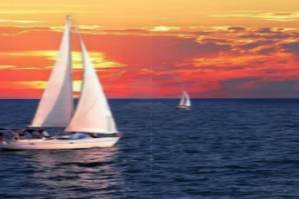 sailboat-sailing-on-a-calm-evening-with-dramatic-sunset