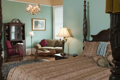 Bedroom with pale blue walls and carved wood 4-poster bed with rich linens, lit chandelier, stuffed chairs and mirror