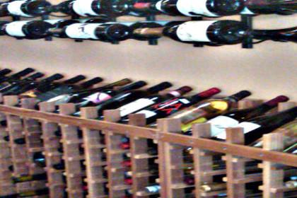 long aisle of wooden wine racks holding multiple bottles of wine