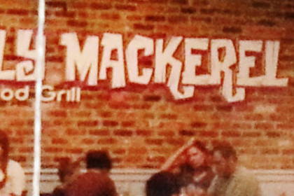 Restaurant interior with red brick wall and white words reading Holy mackerel Seafood Grill