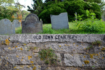three headstones in a grassy lawn, with a low stone sign reading Old Town Cemetery