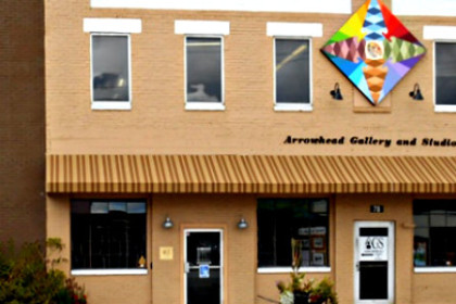 Front of Arrowhead Gallery which is a tan brick building with a colorful quilt block hung above the sign