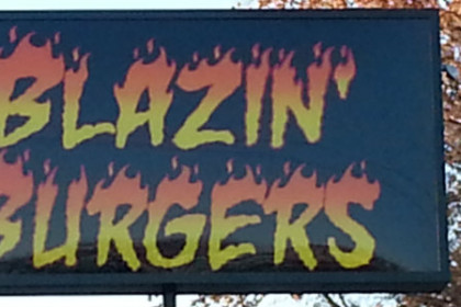 "Large black sign with name of restaurant ""Blazin Burgers"" in yellow and orange, looking like the tops of the letters are on fire."