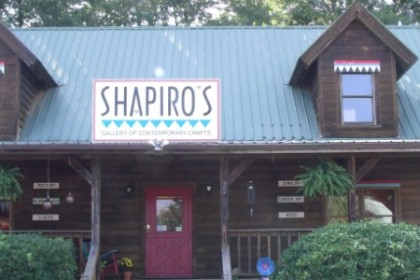 2 story house with dormer windows and a sign above the purple door reading Shapiro's