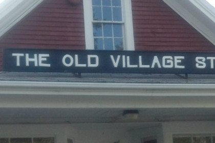 "Red Clapboard building with black sign with white letters reading ""The Old Village Store""."
