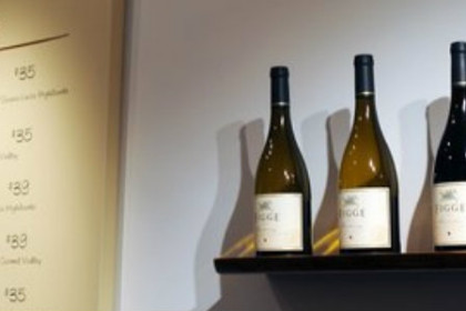 white wall with shelf with 3 bottles of wine and pale yellow price sign for the wines to the left