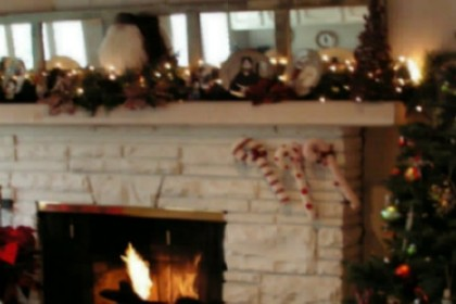 stone fireplace with fire mantle decorated with greenery lighted garland with a stuffed santa doll in the middle of the mantle and decorated christmas tre on the right of the fireplace