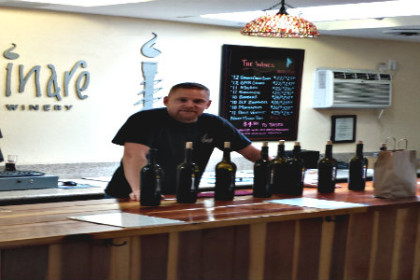 People at tasting bar with owner Aaron Hill, behind the bar