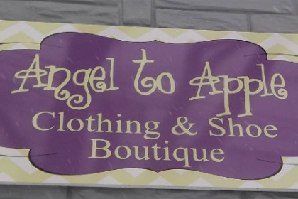 "purple sign with yellow writing "" Angel to Apple Clothing and Shoe Boutique"""