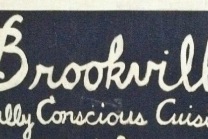 Chalk board sign with Brookville written in white, with Locally sourced cuisine also written in white