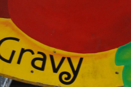 Colorful sign trimed in yellow with red tomatoes reading Red Gravy in the yellow border