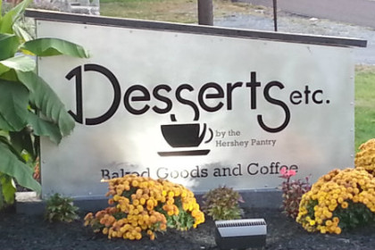 white horizontal sign reading Desserts Etc. with yellow flowers at the base of the sign