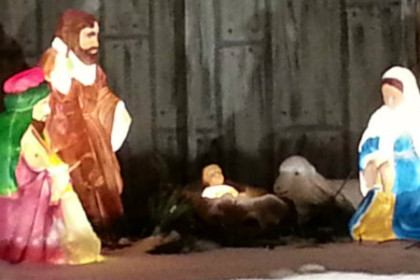 Brightly colored picture of the Navity scene at Cgristmas in the park, Mary, Joseph, Baby Jesus in the manger with animals surrounding