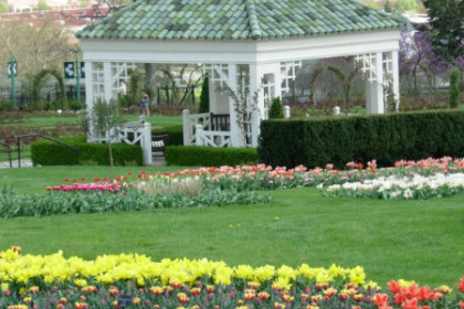 1 story white building with lush lawns and color gardens in the fore ground