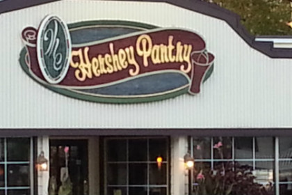 building exterior with wide white roofline and sign reading Hershey Pantry