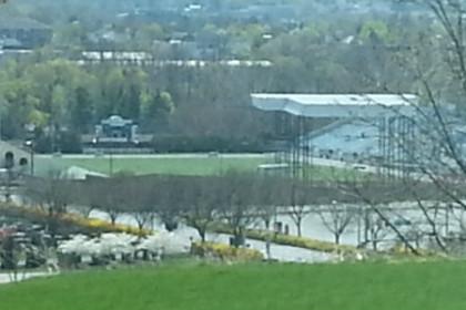 View of Hersheypark Stadium past a grassy yard and trees
