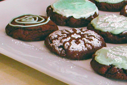 Plate of mint chocolate chip chocolate cookies with mint green icing and sprinkles