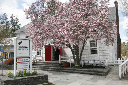 1 story white painted building with red doors standing open and a flowering tree in the front yard.
