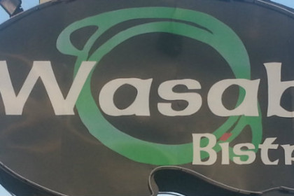 Curved gray sign with white lettering reading Wasabi Bistro