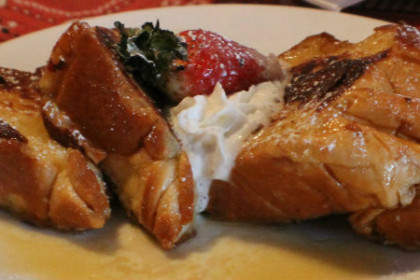 triangle slices of french toast on white plate sitting on red bandana-style table cloth