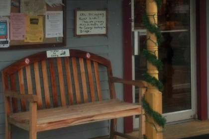 Outside view of Birdwatcher's General Store in orleans, MA with wooden benches and bulitin board covered with signs and photos.
