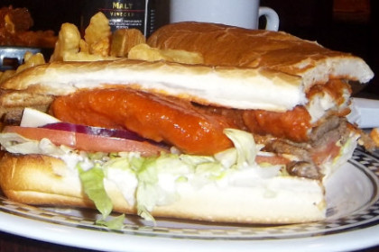 a 12 inch chicken finger stinger sub and fries with hot wings just visible behind