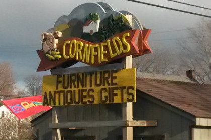 "A road sign that reads ""Cornfields"" at the top, then ""Furniture, Antiques and Gifts"" beneath. There's a smiling corn cob and in image of a barn on the sign as well."